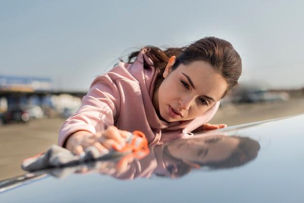Mujer limpiando el capó de la vista frontal del coche Foto gratis