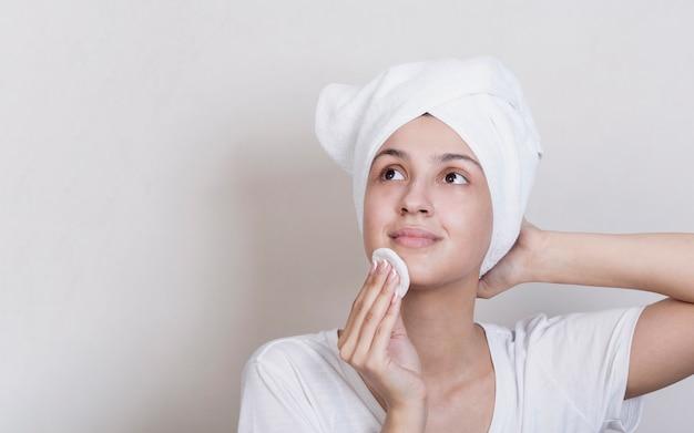 Mujer limpiando su cara con espacio de copia Foto gratis