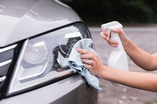 Mujer, limpieza, faros del coche Foto gratis