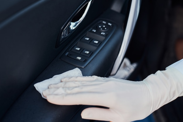 Mujer limpieza interior del coche. mano con toallita antibacteriana desinfectar coche Foto Premium