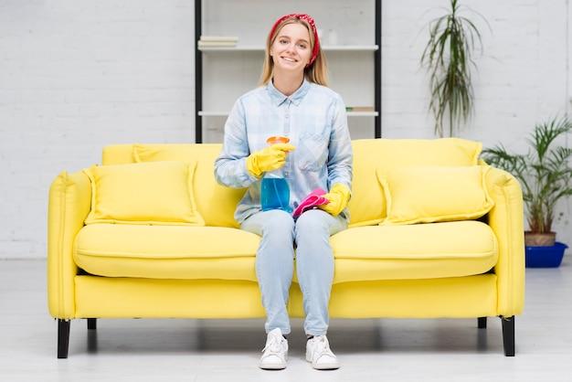 Mujer de limpieza sentada en el sofá Foto gratis