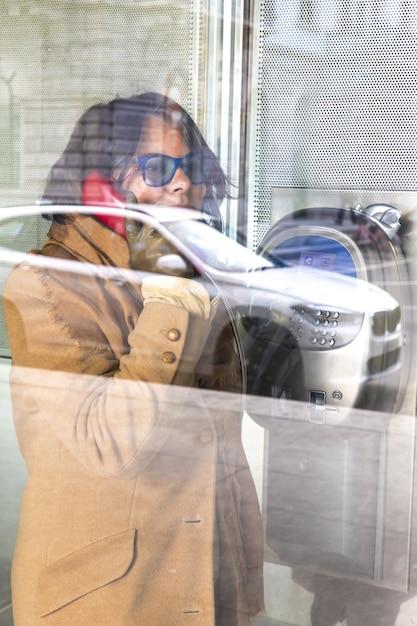 Mujer en una llamada en una cabina de teléfono de cristal con un reflejo de un coche en la calle Foto gratis
