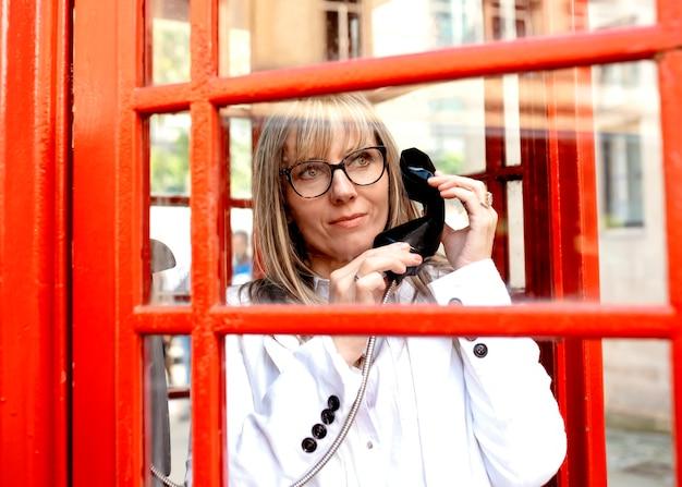 Una mujer llamando desde una cabina de teléfono roja en el centro de la ciudad. Foto Premium