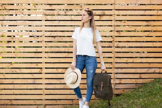 Mujer llevando su mochila y mirando a otro lado Foto gratis