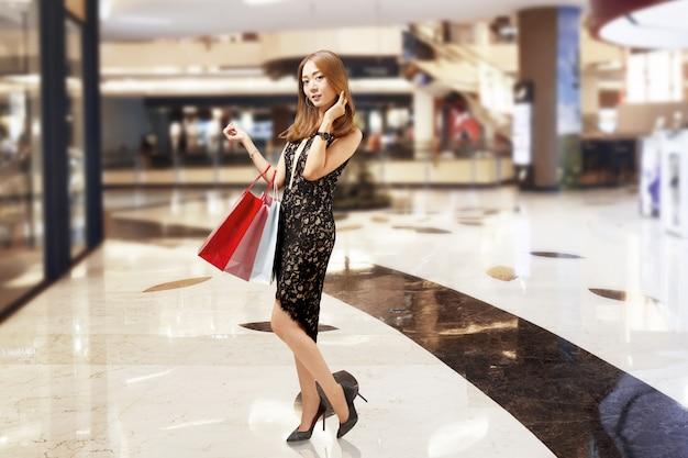 Mujer de lujo asiática atractiva en el vestido negro que