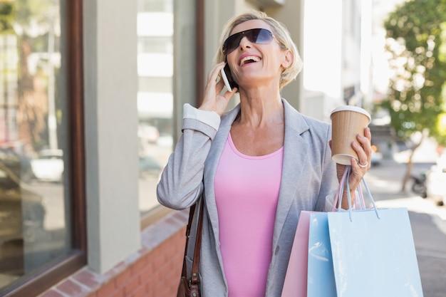 Mujer madura feliz caminando con sus compras de compras Foto Premium