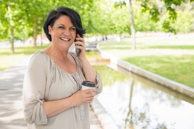 Mujer madura feliz hablando por teléfono móvil Foto gratis