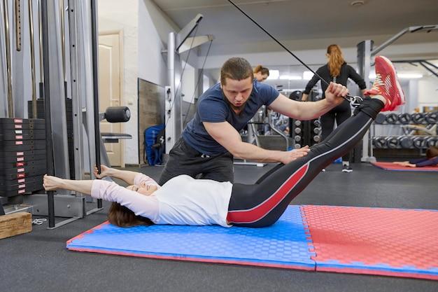 Mujer madura haciendo ejercicio en simuladores de descompresión con rehabilitación de entrenador Foto Premium
