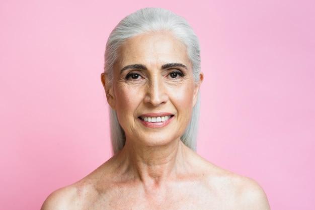 Mujer madura sonriente con fondo rosa Foto gratis