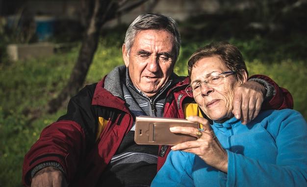 Mujer madura con teléfono inteligente abrazada por su marido mientras ambos sentados en el parque. Foto Premium