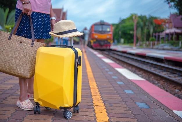 Mujer con maleta de viaje en la estación de tren f840e3456b7