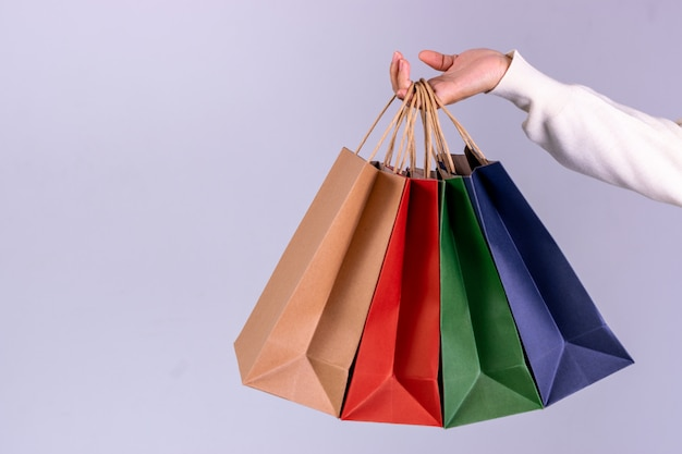 Mujer mano bolsas de papel con espacio de copia. concepto de viernes negro o lunes cibernético. Foto Premium