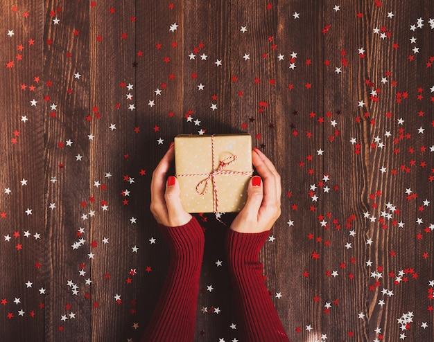 Mujer en la mano con caja de regalo de navidad Foto gratis