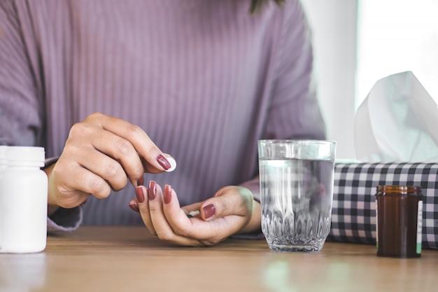 Mujer mano preparando medicina con agua Foto Premium