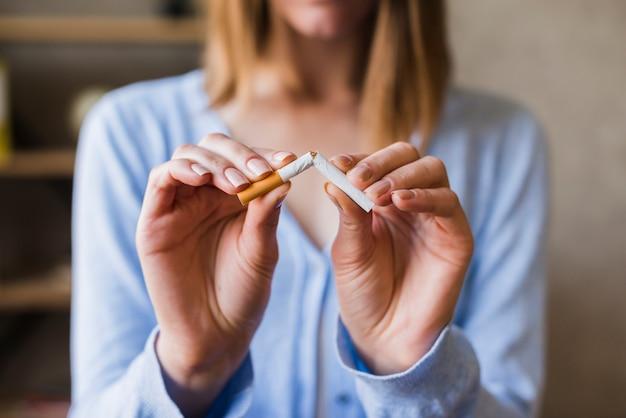 Mujer mano rompiendo cigarrillo Foto gratis
