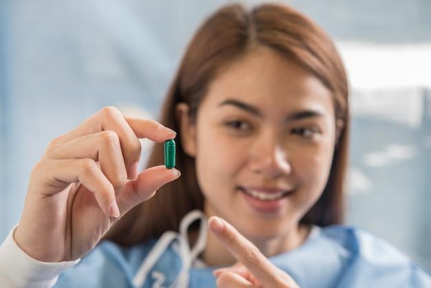 Mujer mano sosteniendo una pastillas tomar medicina de acuerdo con la orden del médico Foto gratis