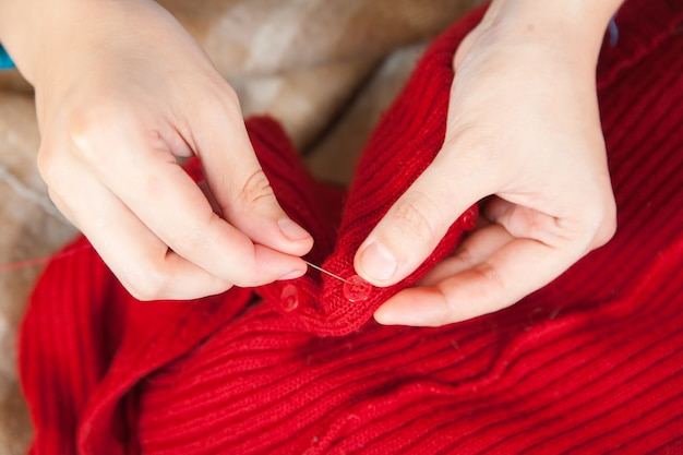 Mujer manos cosiendo un botón Foto Gratis