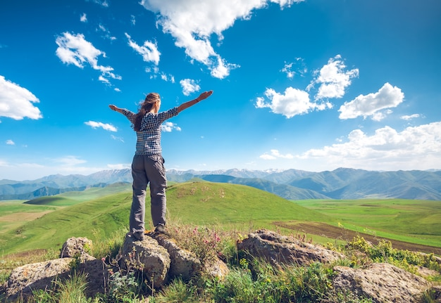 Mujer con manos levantadas en colinas Foto Premium
