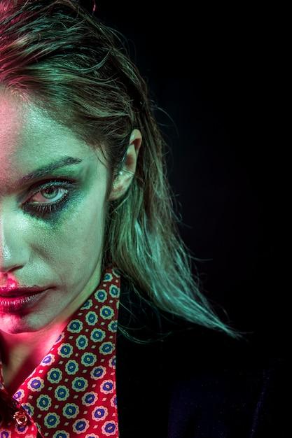 Mujer con maquillaje de media cara de joker de halloween Foto gratis
