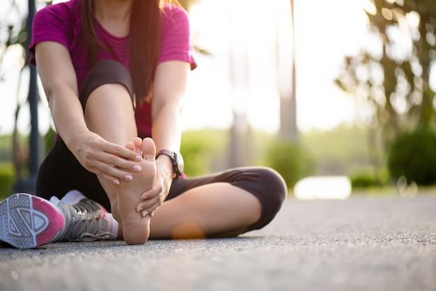 Mujer masajeando su pie doloroso mientras hace ejercicio. concepto de lesiones deportivas. Foto Premium