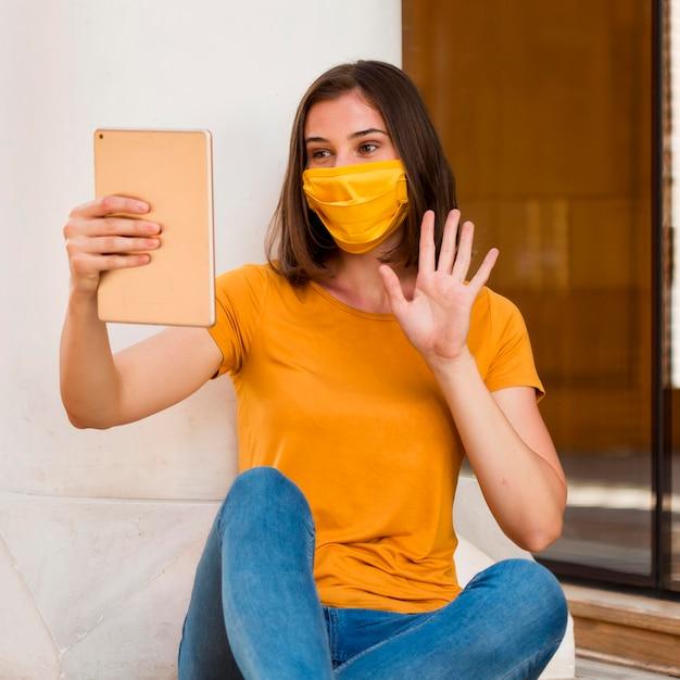 Mujer con máscara amarilla saludando a tableta Foto gratis