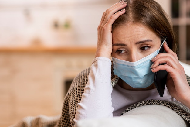 Mujer con máscara en cuarentena hablando por teléfono Foto Premium
