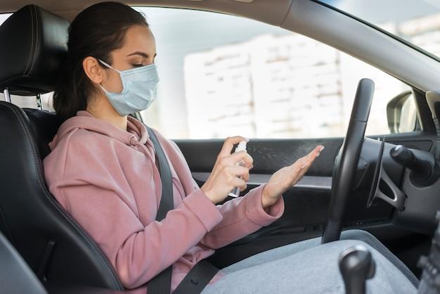 Mujer con máscara y desinfectante para manos Foto gratis