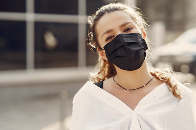Mujer en una máscara se encuentra en la calle Foto gratis