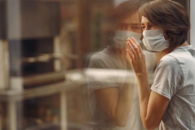 Mujer en una máscara está junto a la ventana Foto gratis