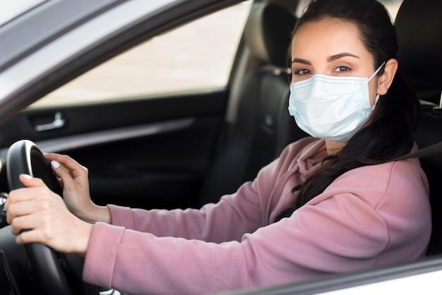 Mujer con máscara médica en coche Foto Premium