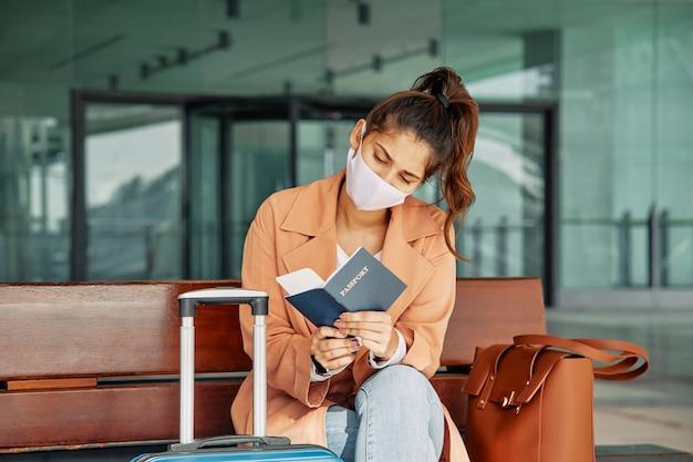Mujer con máscara médica comprobando su pasaporte en el aeropuerto durante la pandemia Foto gratis