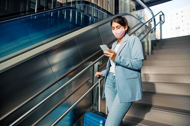 Mujer con máscara médica y equipaje con smartphone mientras sube escaleras durante la pandemia Foto gratis