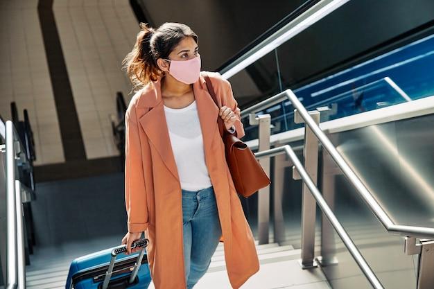 Mujer con máscara médica y equipaje subiendo escaleras en el aeropuerto durante la pandemia Foto gratis