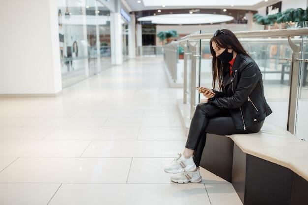 Mujer con máscara negra médica y teléfono móvil en un centro comercial. pandemia de coronavirus. una mujer con una máscara está de pie en un centro comercial. una mujer con una máscara protectora está de compras en el centro comercial Foto Premium