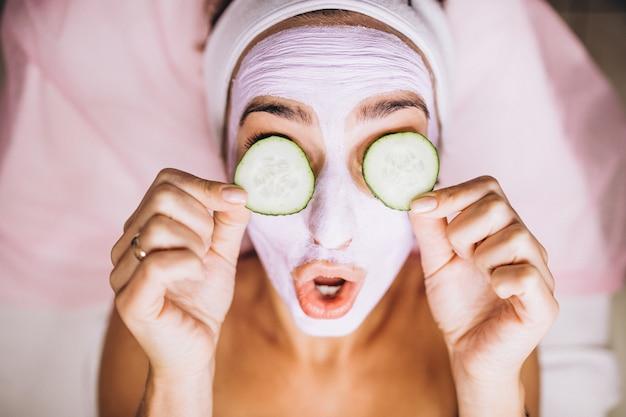 Mujer con máscara y pepino en los ojos Foto gratis