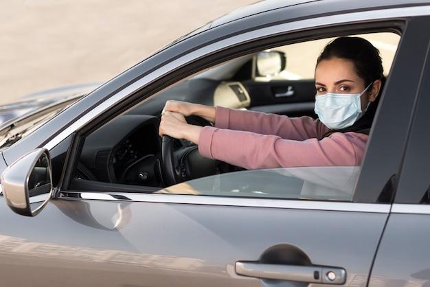 Mujer con máscara de protección en el auto Foto gratis
