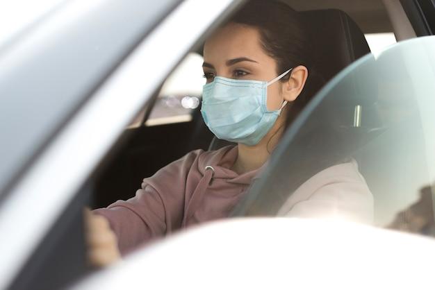 Mujer con máscara de protección en coche Foto Premium