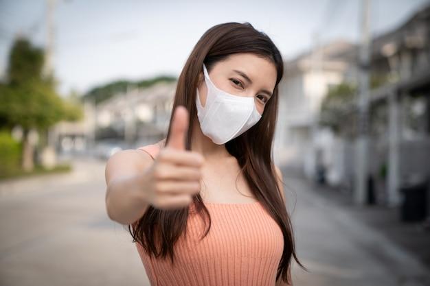 Mujer con máscara protectora, mostrando los pulgares para arriba. Foto Premium