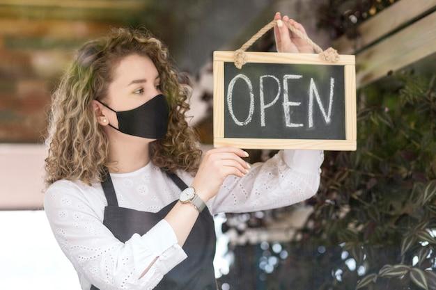 Mujer con máscara sosteniendo pizarra con abierto Foto Premium