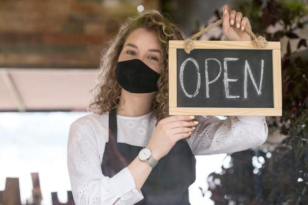 Mujer con máscara sosteniendo pizarra con texto abierto Foto gratis