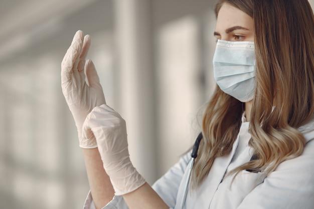 Mujer en una máscara y uniforme se pone guantes Foto gratis