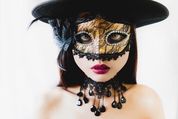 Mujer con una máscara veneciana dorada y un sombrero negro en un ... 3ad51ae6882