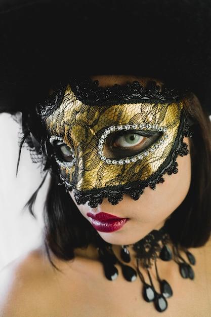 Mujer con una máscara veneciana dorada y un sombrero negro en un fondo  blanco  3d25dccf0a0