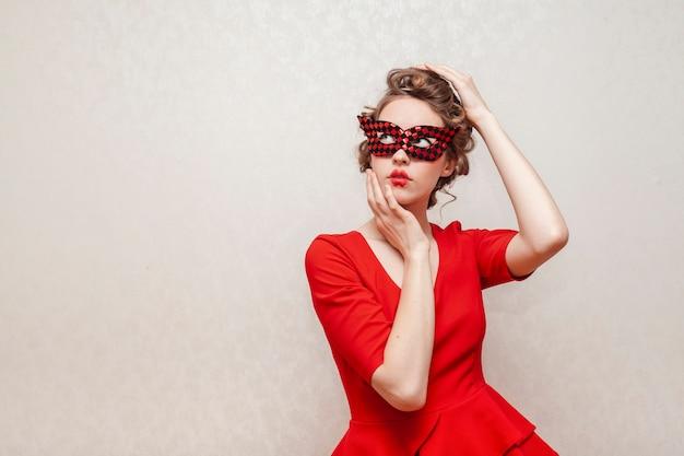 Mujer con máscara y vestido rojo posando Foto gratis