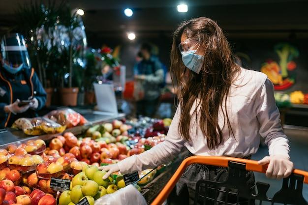 La mujer con mascarilla va a comprar manzanas Foto gratis