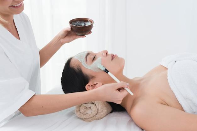 Mujer con una mascarilla facial en un spa Foto gratis