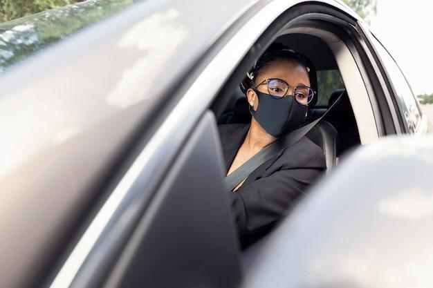 Mujer con mascarilla mirando en el espejo mientras conduce su coche Foto gratis
