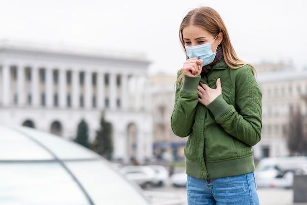 Mujer con mascarilla quirúrgica en espacios públicos Foto Premium