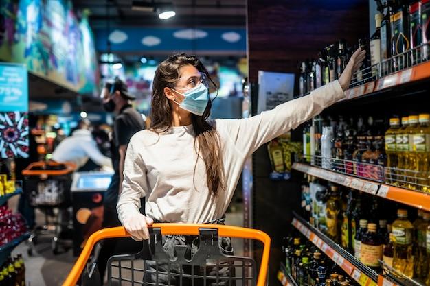 Mujer con mascarilla quirúrgica y guantes está comprando en el supermercado después de la pandemia de coronavirus. la chica con mascarilla quirúrgica va a comprar comida. Foto gratis
