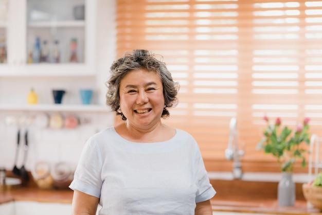 Mujer mayor asiática que siente la sonrisa feliz y que mira a la cámara mientras que relájese en cocina en casa. Foto gratis